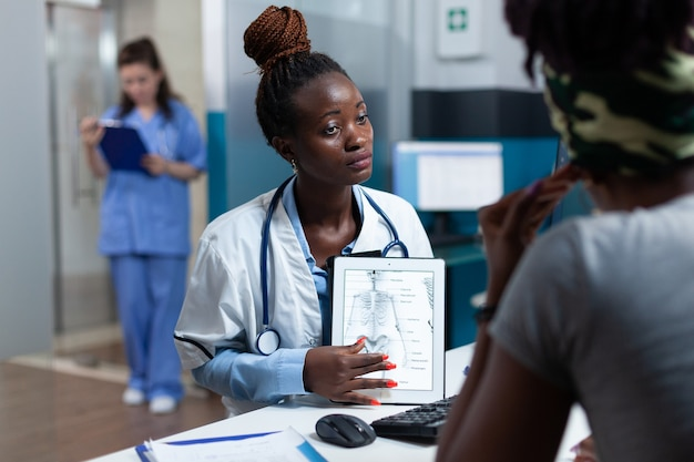 Afroamerykański lekarz wyjaśniający radiografię