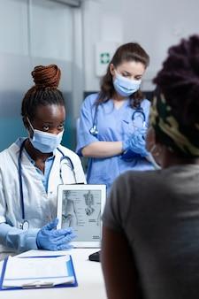 Afroamerykański lekarz z maską przeciw koronawirusowi wyjaśniający radiografię kości