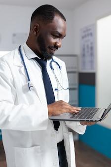 Afroamerykański lekarz ze stetoskopem wpisuje wiedzę medyczną na laptopie