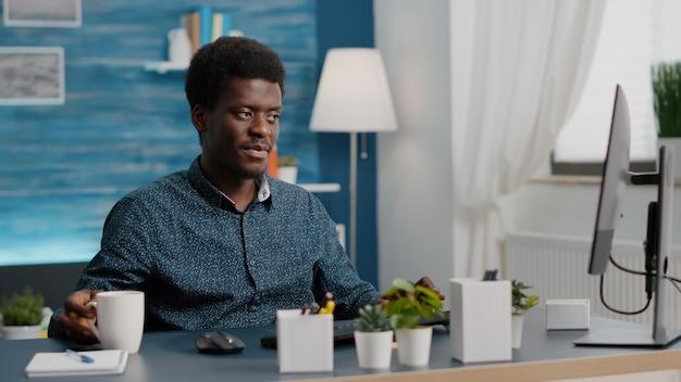 Afroamerykański menedżer pracujący w domu popijając kawę i pisząc na komputerze