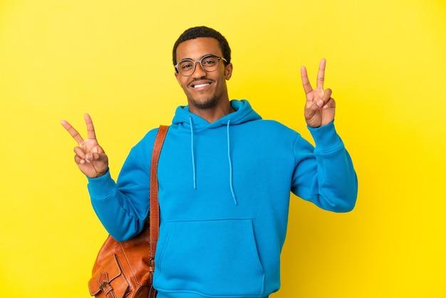 Afroamerykański mężczyzna student na na białym tle żółtym tle pokazując znak zwycięstwa obiema rękami