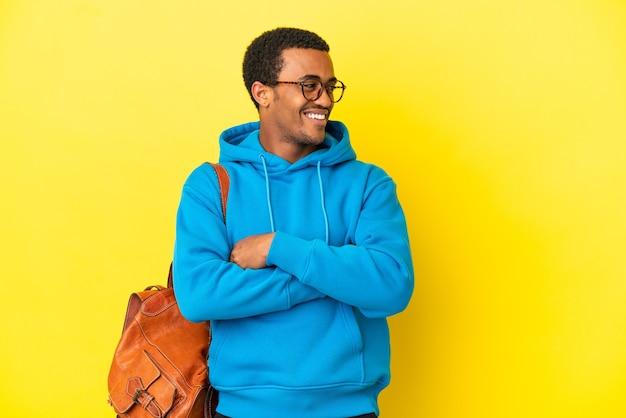 Afroamerykański mężczyzna student na odosobnionym żółtym tle szczęśliwy i uśmiechnięty