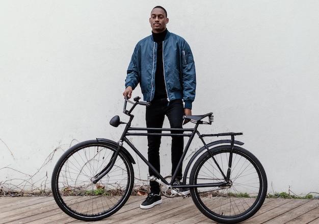 Afroamerykański mężczyzna trzymający rower przed sobą