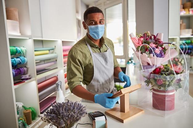 Afroamerykański mężczyzna w ochronnej masce szpitalnej i rękawiczkach kładzie ręce na stojaku z tabletem