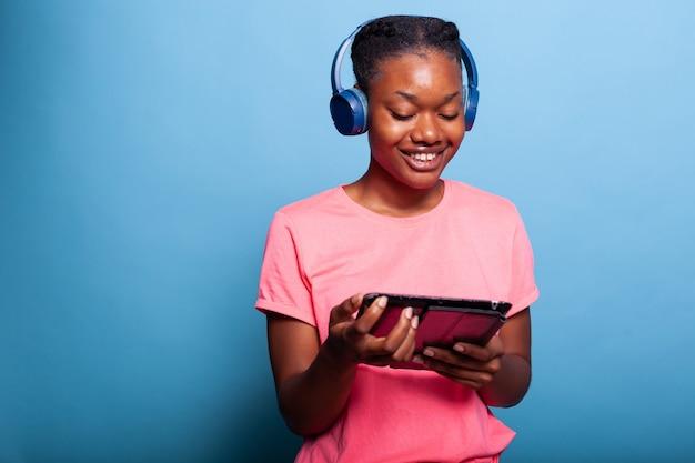 Afroamerykański nastolatek ze słuchawkami, trzymający komputer typu tablet