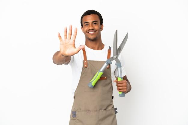Afroamerykański ogrodnik mężczyzna trzymający nożyce do przycinania na białym tle, licząc pięć palcami