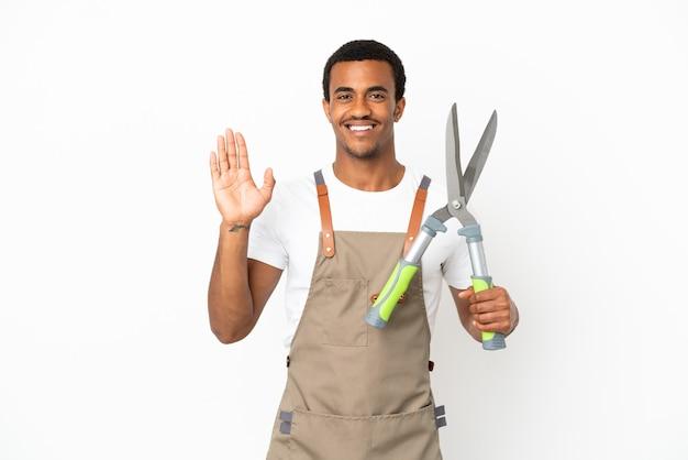 Afroamerykański ogrodnik mężczyzna trzymający nożyce do przycinania na na białym tle pozdrawiając ręką ze szczęśliwym wyrazem twarzy