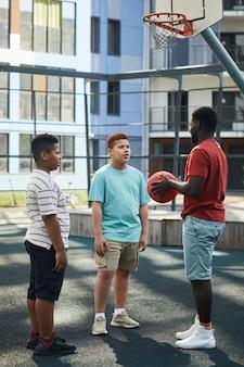 Afroamerykański ojciec z koszykówką rozmawiający z chłopcami na placu zabaw na tle nowoczesnego budynku