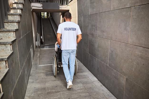 Afroamerykański opiekun w lekkich ubraniach toczący wózek inwalidzki z niepełnosprawną starzejącą się kobietą po pochyłej ścieżce