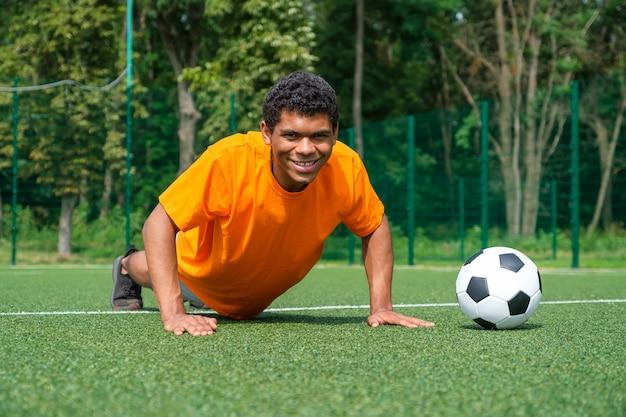 Afroamerykański piłkarz rozgrzewa się na treningach na boisku latem