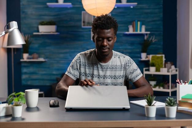 Afroamerykański pracownik biznesowy otwierający komputer przenośny