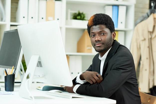 Afroamerykański profesjonalista pozuje w biurze