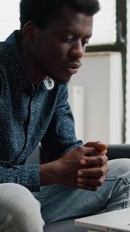 Afroamerykański przedsiębiorca podczas zdalnej rozmowy wideo ze swojego salonu