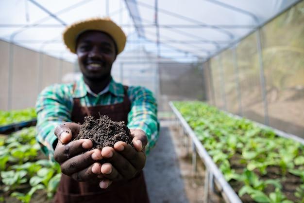 Afroamerykański rolnik trzymający ziemię w dłoniach w szklarni