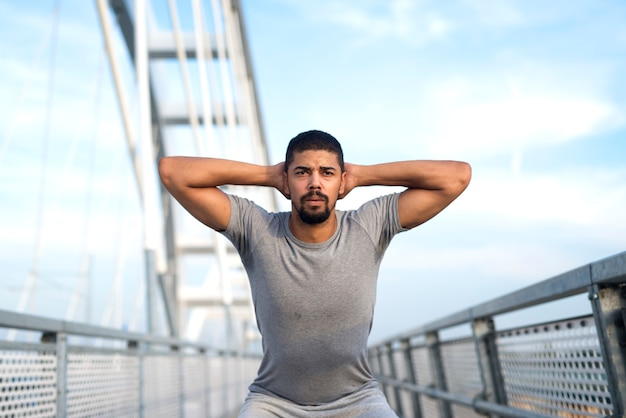 Afroamerykański sportowiec rozgrzewający swoje ciało przed treningiem na świeżym powietrzu