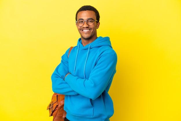 Afroamerykański student mężczyzna nad odosobnionym żółtym tłem w okularach i uśmiechnięty