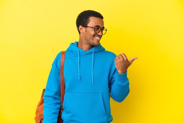 Afroamerykański student mężczyzna nad odosobnionym żółtym tłem, wskazując na bok, aby zaprezentować produkt