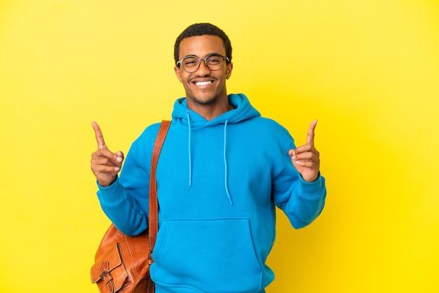 Afroamerykański student mężczyzna nad odosobnionym żółtym tłem, wskazując na świetny pomysł