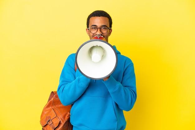 Afroamerykański student na białym tle krzyczy przez megafon