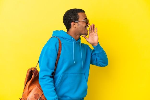 Afroamerykański student na białym tle krzyczy z szeroko otwartymi ustami na boki