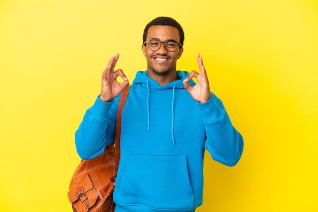 Afroamerykański student na białym tle pokazujący znak ok palcami