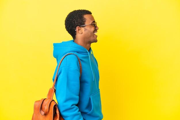 Afroamerykański student na białym tle, śmiejący się w pozycji bocznej