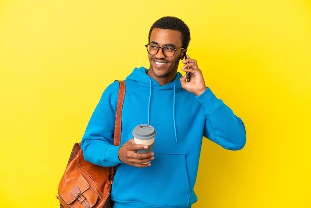 Afroamerykański student na białym tle, trzymający kawę na wynos i telefon komórkowy
