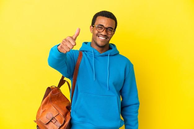 Afroamerykański student na białym tle z kciukami do góry, ponieważ wydarzyło się coś dobrego