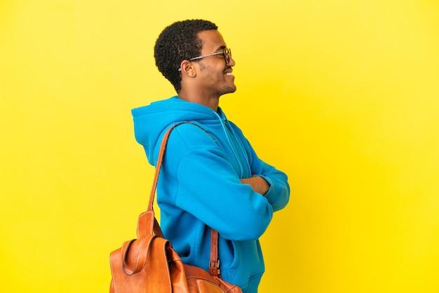 Afroamerykański student na białym tle żółtym tle w pozycji bocznej