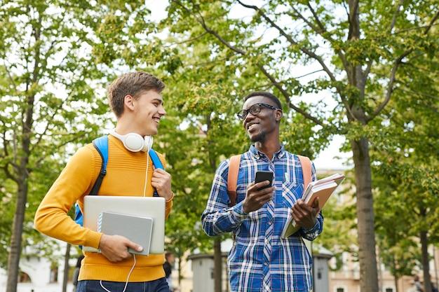 Afroamerykański student na czacie z przyjacielem na zewnątrz
