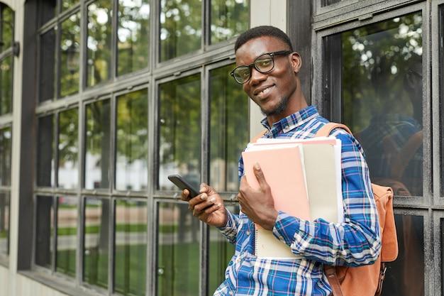 Afroamerykański student pozuje w kampusie