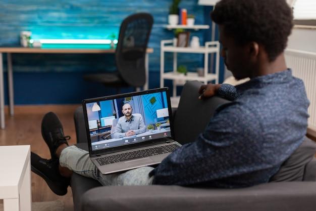 Afroamerykański student prowadzący webinarium w szkole zarządzania online