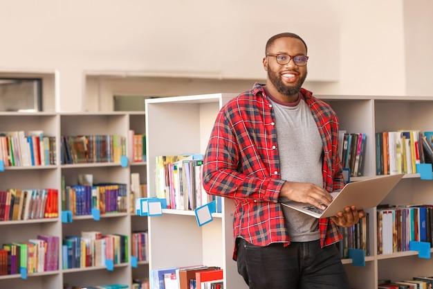 Afroamerykański student przygotowujący się do egzaminu w bibliotece