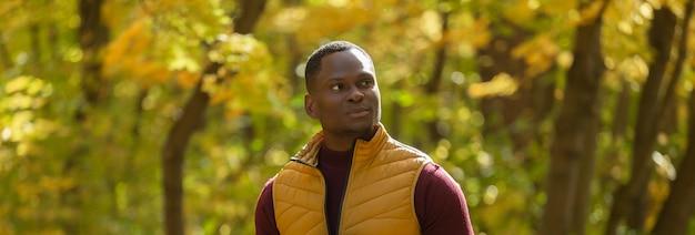 Afroamerykański student spacerujący po parku w jesiennym sezonie transparent z miejscem na kopię dla