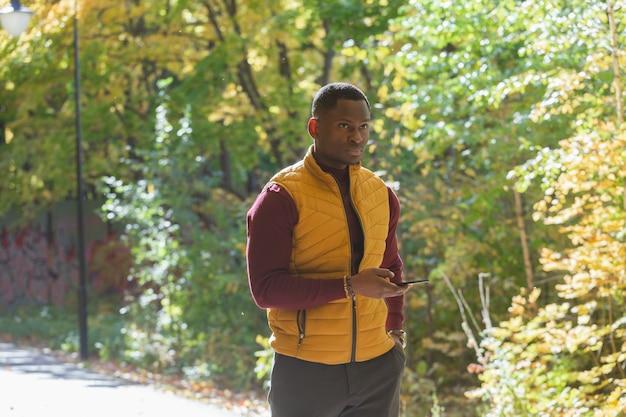 Afroamerykański student spacerujący po parku w sezonie jesiennym