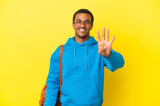 Afroamerykański student student na odizolowanym żółtym tle szczęśliwy i liczący cztery palcami