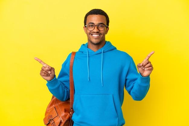 Afroamerykański student student na odosobnionym żółtym tle, wskazując palcem na boki i szczęśliwy