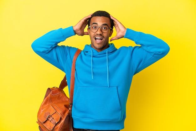 Afroamerykański student student na odosobnionym żółtym tle z wyrazem niespodzianki