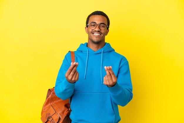 Afroamerykański student student na odosobnionym żółtym tle zarabiania pieniędzy gest