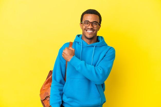 Afroamerykański student świętujący zwycięstwo na odosobnionym żółtym tle