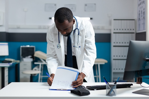 Afroamerykański terapeuta lekarz analizujący dokumenty medyczne