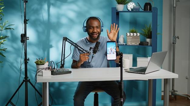 Afroamerykański vloger używający smartfona do kręcenia podcastu