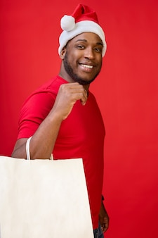 Afroamerykański wesoły uśmiecha się słodko w kapeluszu świętego mikołaja i trzyma w rękach białe papierowe torby