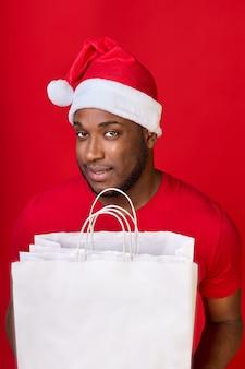 Afroamerykański wesoły uśmiecha się w kapeluszu świętego mikołaja i trzyma białe papierowe torby na czerwonym tle