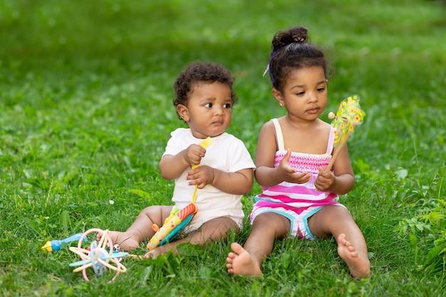Afroamerykańskie dzieci, chłopiec z dziewczynką lub brat i siostra bawią się latem na zielonym trawniku