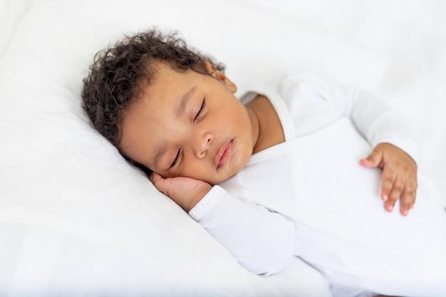Afroamerykańskie małe dziecko śpi na białym łóżku w domu z ręką założoną pod policzkiem