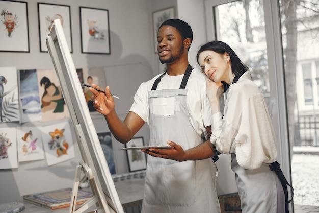 Afrykanin i kobieta w klasie malarstwa, rysując na sztalugach.