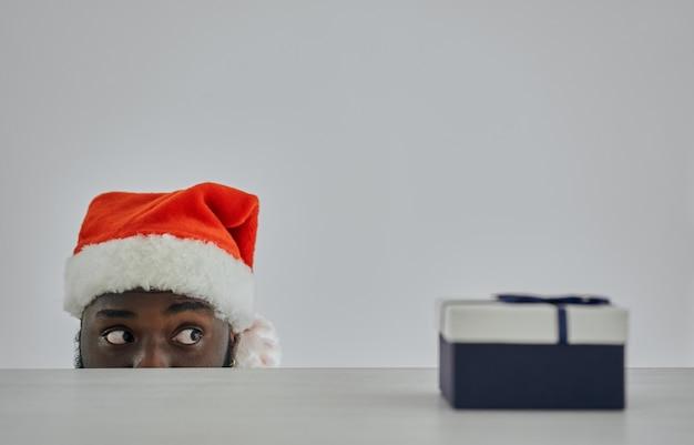 Afrykanin w czapce mikołaja oglądający ze stołu z prezentem