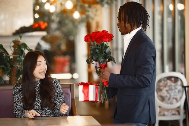 Afrykanin w garniturze. dziewczyna jest szczęśliwa. bukiet pięknych kwiatów i prezent