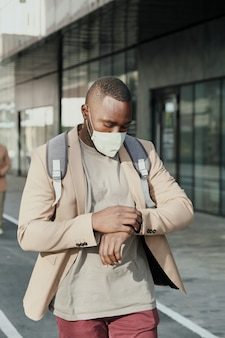 Afrykanin w masce ochronnej idący ulicą i patrząc na zegarek spieszy się z pracą